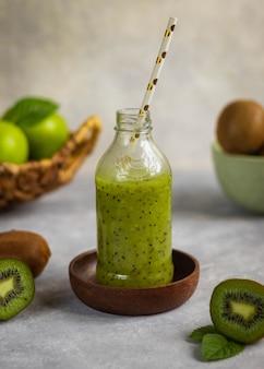 Gezonde groene fruitsmoothie met groene appel, kiwi en melissa in de fles op grijze achtergrond