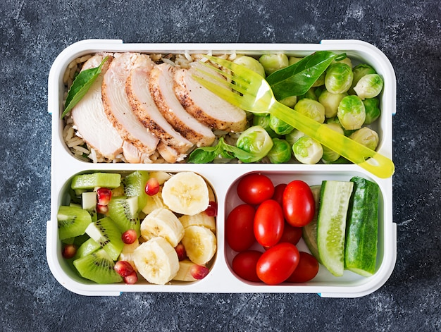 Gezonde groene maaltijd prep containers met kipfilet, rijst, spruitjes, groenten en fruit