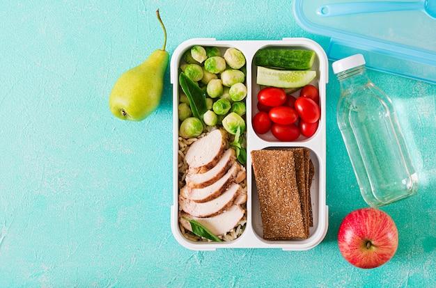 Gezonde groene maaltijd prep containers met kippenfilet, rijst, spruitjes en groenten luchtschot met exemplaarruimte. diner in lunchbox. bovenaanzicht plat leggen