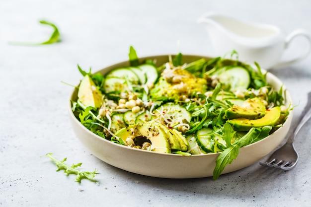 Gezonde groene salade met avocado, komkommer en rucola in witte schotel.