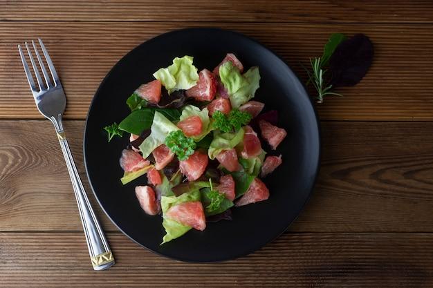 Gezonde groene salade met grapefruit, weeg voedsel. dieet plan. houten rustieke tafel.