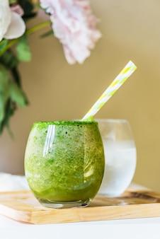 Gezonde groene smoothie en pioenrozen