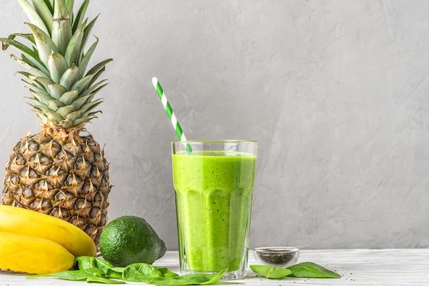 Gezonde groene smoothie in een glas met een rietje gemaakt van spinazie, ananas, avocado, banaan en chiazaad