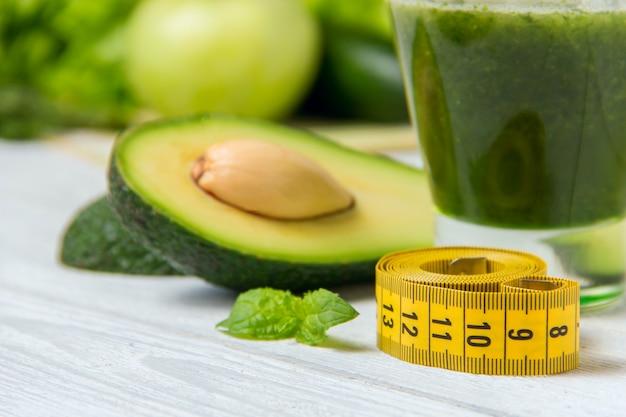 Gezonde groene smoothie met ingrediënten op wit hout