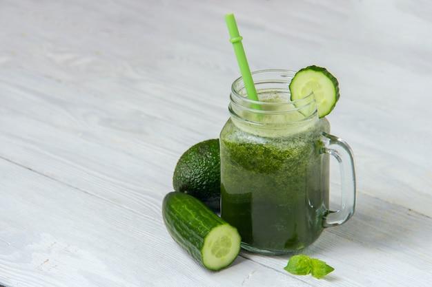 Gezonde groene smoothie met ingrediënten op witte houten achtergrond