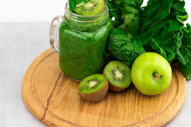 Gezonde groene smoothie met spinazie in een potmok met ingrediënten op houten ondergrond.