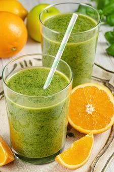 Gezonde groene smoothie met spinazie, mango, sinaasappel, limoen, appel, citron in glazen potten.