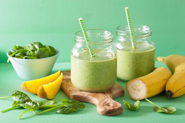 Gezonde groene smoothie met spinazie mangobanaan in glazen potten