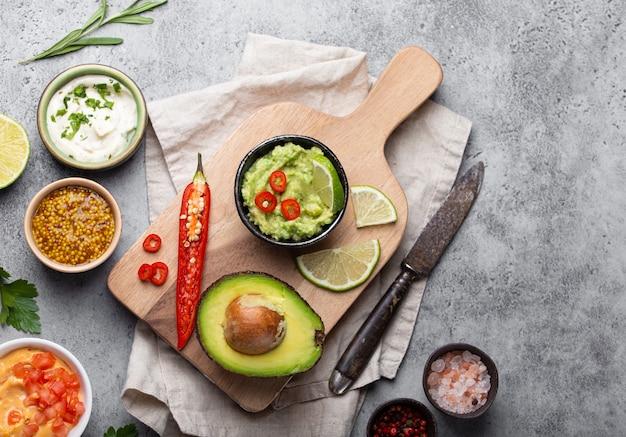 Gezonde groene vegan guacamole saus maken met verse avocado, limoen, chili peper op houten snijplank met oud mes, stenen rustieke achtergrond, bovenaanzicht, close-up. traditionele mexicaanse saus