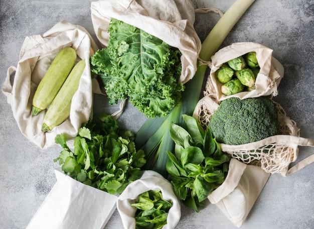 Gezonde groene veganistingrediënten voor het koken. diverse schone groene groenten en kruiden in textielzakken. producten uit de markt zonder plastic. zero waste concept flat lag.