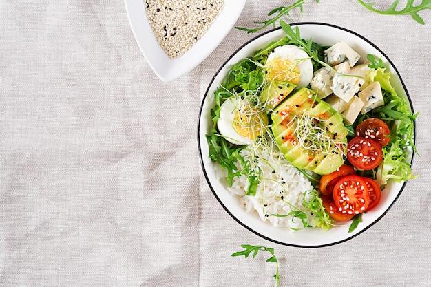 Gezonde groene vegetarische boeddha kom lunch met eieren, rijst, tomaat, avocado en blauwe kaas op tafel.