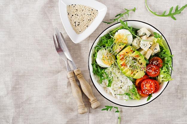 Gezonde groene vegetarische boeddha kom lunch met eieren, rijst, tomaat, avocado en blauwe kaas op tafel