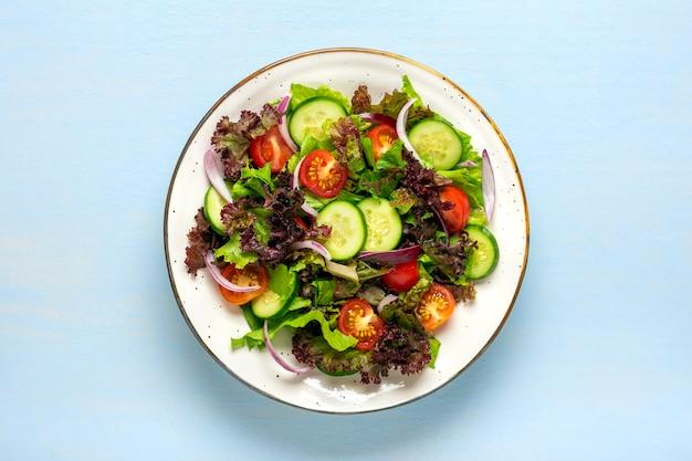 Gezonde groentesalade van kerstomaatjes, plakjes komkommer, groene en paarse slablaadjes, uien en olijfolie in plaat op blauwe houten tafel bovenaanzicht plat leggen dieet, mediterraan menu veganistisch eten.