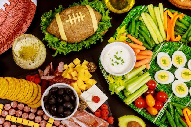 Gezonde groenteschotel met gehaktbrood als een voetbal voor een american football-gamel-fanfeest.