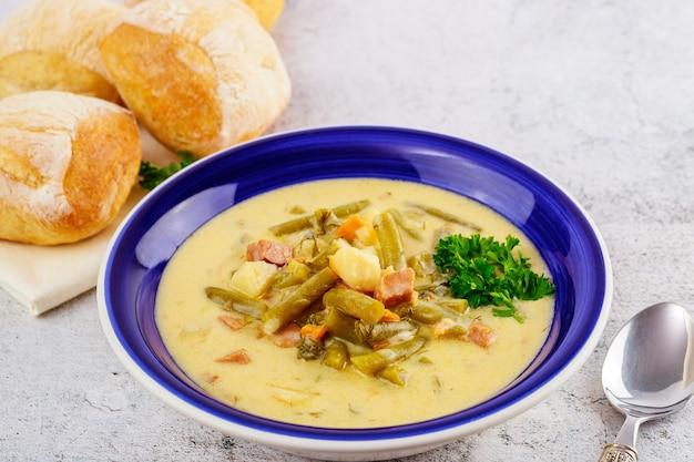 Gezonde groentesoep met brood in blauw bord.