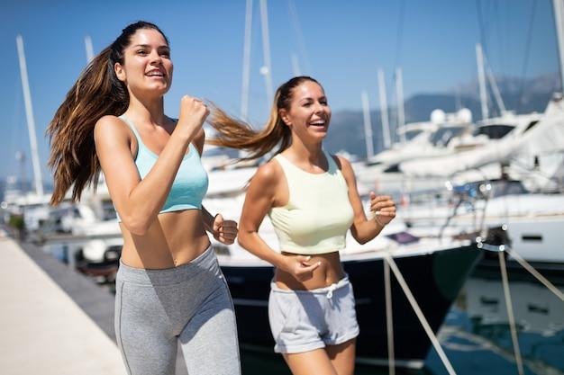 Gezonde groep vrienden die samen rennen en genieten van vriendentijd
