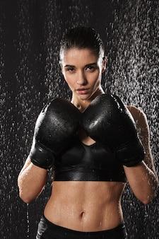 Gezonde gymnastiek- vrouw die in handschoenen kickboxing en zich in aanvalspositie onder regendalingen bevinden, die over zwarte achtergrond wordt geïsoleerd