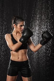 Gezonde gymnastische vrouw met slank perfect lichaam kickboksen in handschoenen en permanent in de verdediging positie onder regendruppels, geïsoleerd op zwarte achtergrond