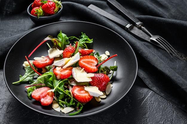 Gezonde heerlijke salade met camembert, aardbeien, noten, snijbiet en rucola