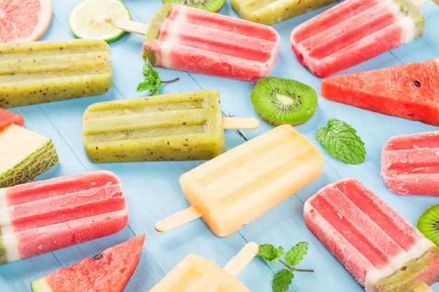 Gezonde hele fruit ijslollys met bessen kiwi watermeloen meloen op houten vintage tafel