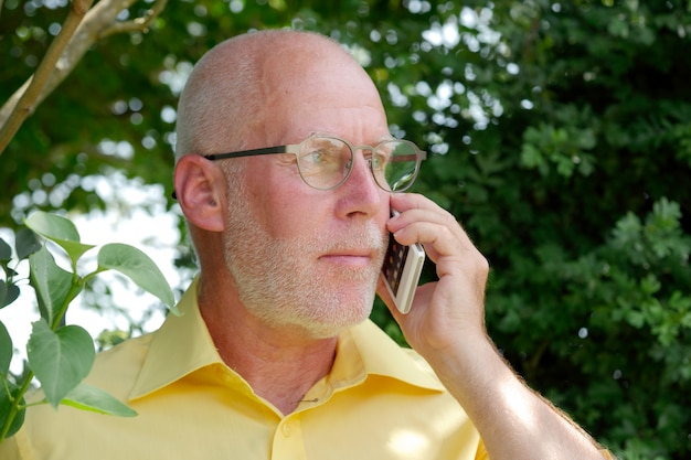 Gezonde hogere mens op de telefoon openluchttuin