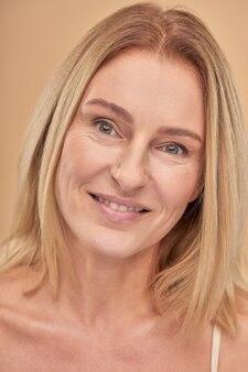 Gezonde huid close-up portret van een charmante, gelukkige volwassen blanke vrouw die lacht naar de camera terwijl