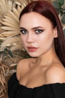 Gezonde huid haar lichaam vrouw natuurlijke schone huid schoonheid make-up lang donkerbruin haar vrouwelijk model, brunette meisje met bordeauxrode lippen op een achtergrond van lente droog veld bloemen. open schouders