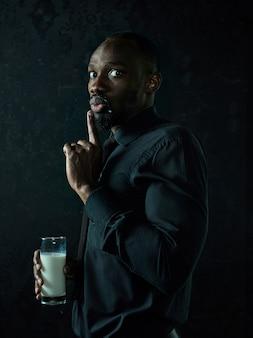Gezonde jonge afrikaanse man holging kopje melk op een bllack studio.