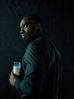 Gezonde jonge afrikaanse man met kopje melk op een zwarte studio achtergrond.
