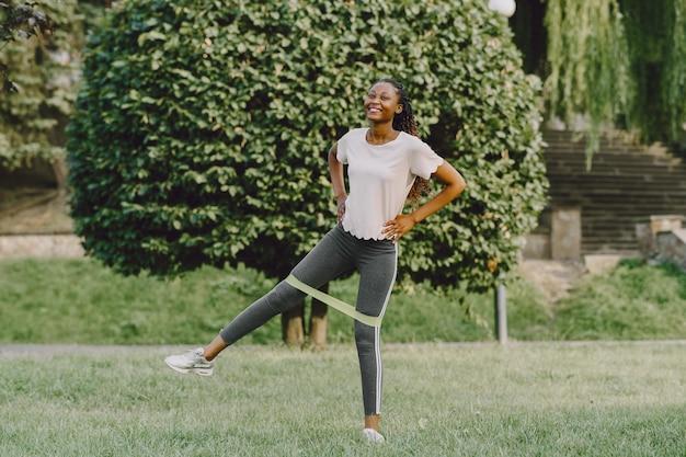Gezonde jonge afrikaanse vrouw buiten in de ochtend. meisje met gum.