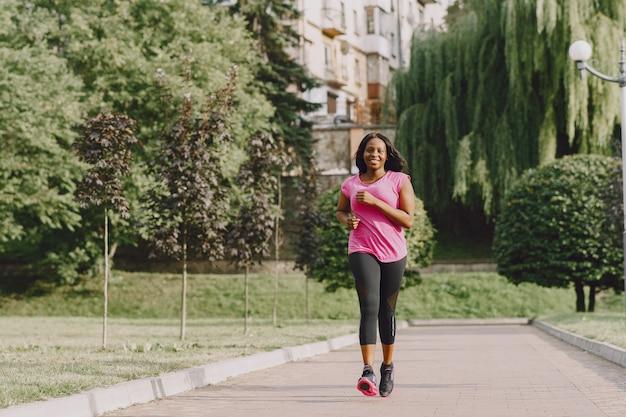 Gezonde jonge afrikaanse vrouw buiten in de ochtend. vrouw in roze t-shirt.