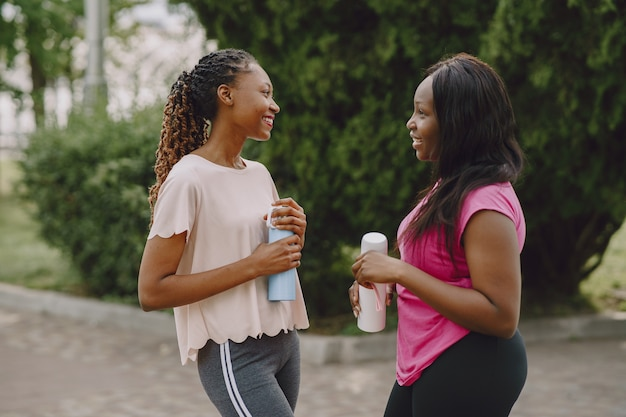 Gezonde jonge afrikaanse vrouwen buiten in ochtendpark. vrienden trainen.