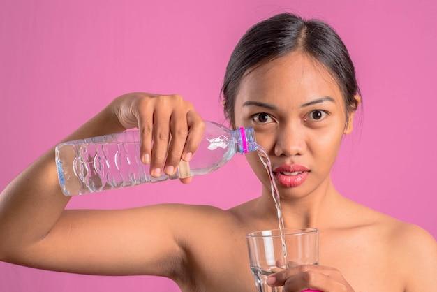 Gezonde jonge aziatische latijnse vrouw met water.