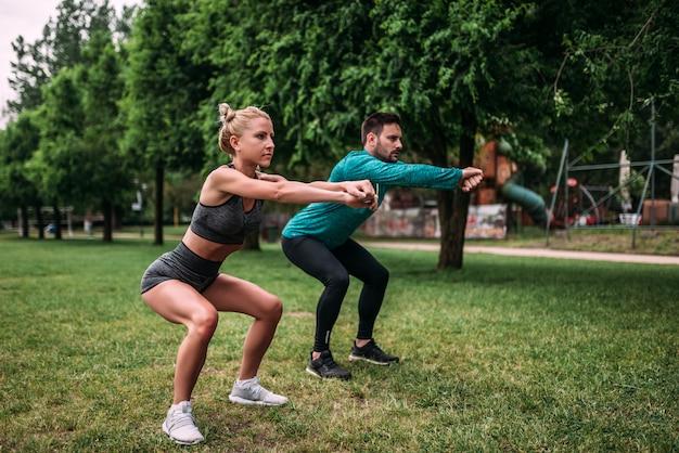 Gezonde jonge man en vrouw die hurkende oefeningen in openlucht doen.