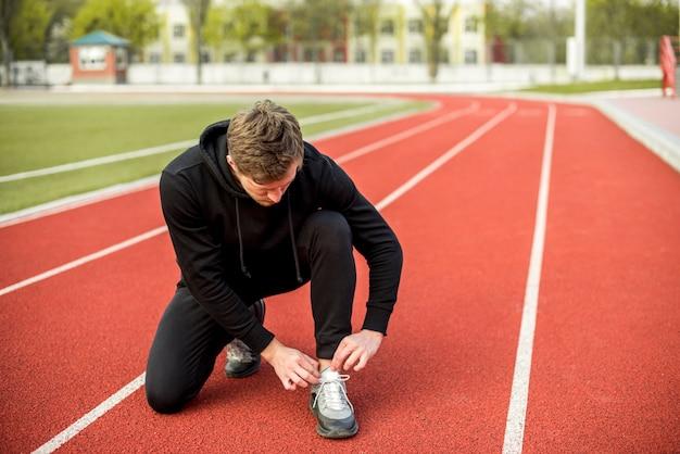 Gezonde jonge mensenzitting op renbaan die zijn schoenveter binden