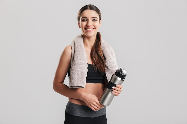 Gezonde jonge sportvrouw die trainingspak met handdoek dragen die en fles met zoet water kijken houden, over grijze muur wordt geïsoleerd