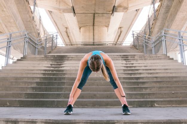 Gezonde jonge vrouw die zich uitstrekt voor fitness en lichaamsbeweging