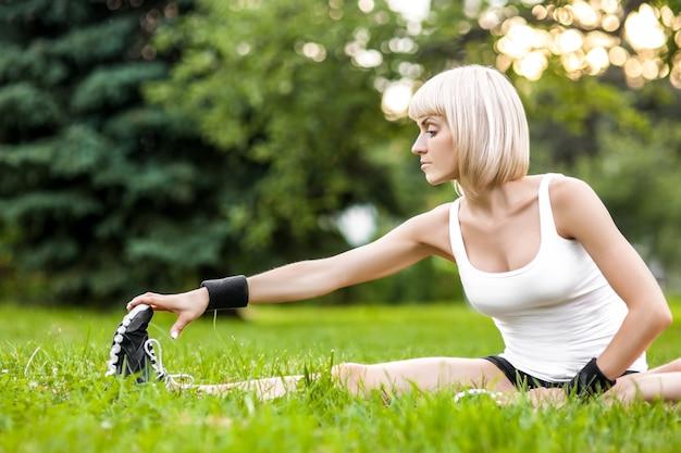 Gezonde jonge vrouw die zich uitstrekt voor fitness en oefening