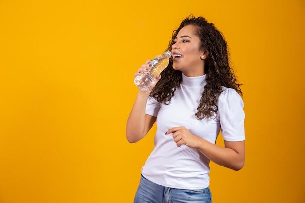 Gezonde jonge vrouw drinkwater op gele achtergrond met ruimte voor tekst.