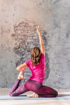 Gezonde jonge vrouw het praktizeren yoga tegen doorstane muur