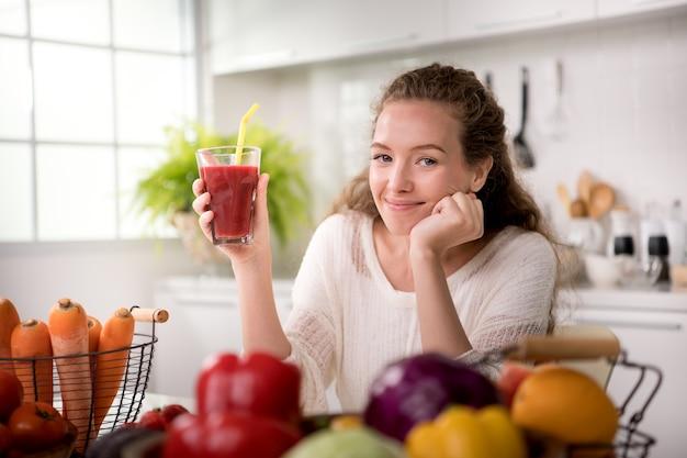 Gezonde jonge vrouw in een keuken met fruit en groenten en sap