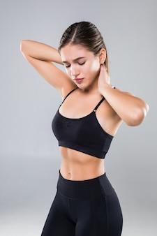 Gezonde jonge vrouw in sportkleding die op witte muur wordt geïsoleerd