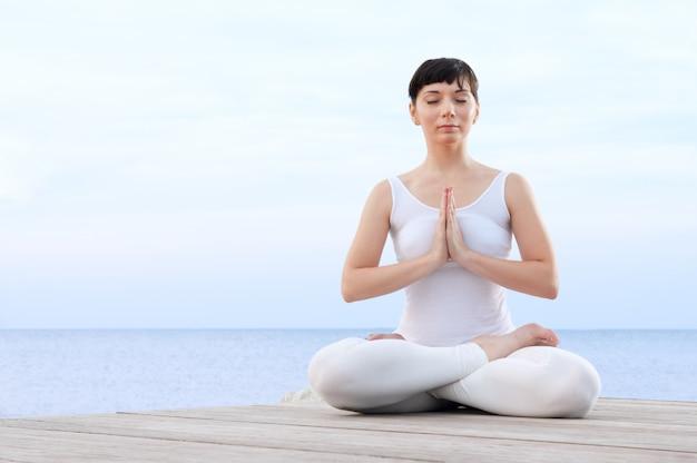 Gezonde jonge vrouw mediteren in yoga lotus houding op zee