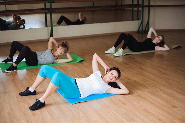 Gezonde jonge vrouwen die oefening op matten voor geschiktheid in de gymnastiek doen.