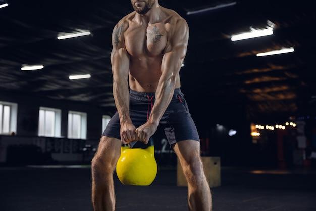 Gezonde jongeman, atleet doen oefeningen met het gewicht in de sportschool. enig kaukasisch model dat hard oefent, zijn lichaam opleidt. concept van een gezonde levensstijl, sport, fitness, bodybuilding, welzijn.