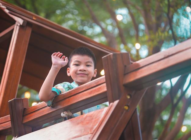 Gezonde jongen zwaaien vanaf de bovenkant van een speeltuin