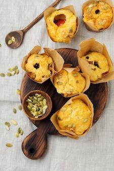 Gezonde kaasmuffins met polenta, kerstomaatjes en pompoenpitten als ontbijt. selectieve aandacht. bovenaanzicht. kopieer ruimte.