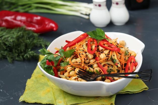 Gezonde kikkererwten, koreaanse wortel, paprika en uiensalade versierd met zwarte sesam