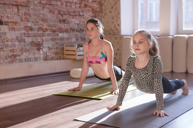 Gezonde kinderen levensstijl. yoga voor kinderen. gymnastiekontwikkeling, tienersport. jonge meisjes in studio, gymnastiekachtergrond, gezondheidsconcept
