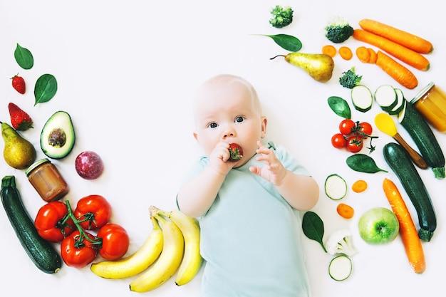Gezonde kindervoeding voedsel achtergrond lachende baby 8 maanden oudbaby eerste vaste voeding